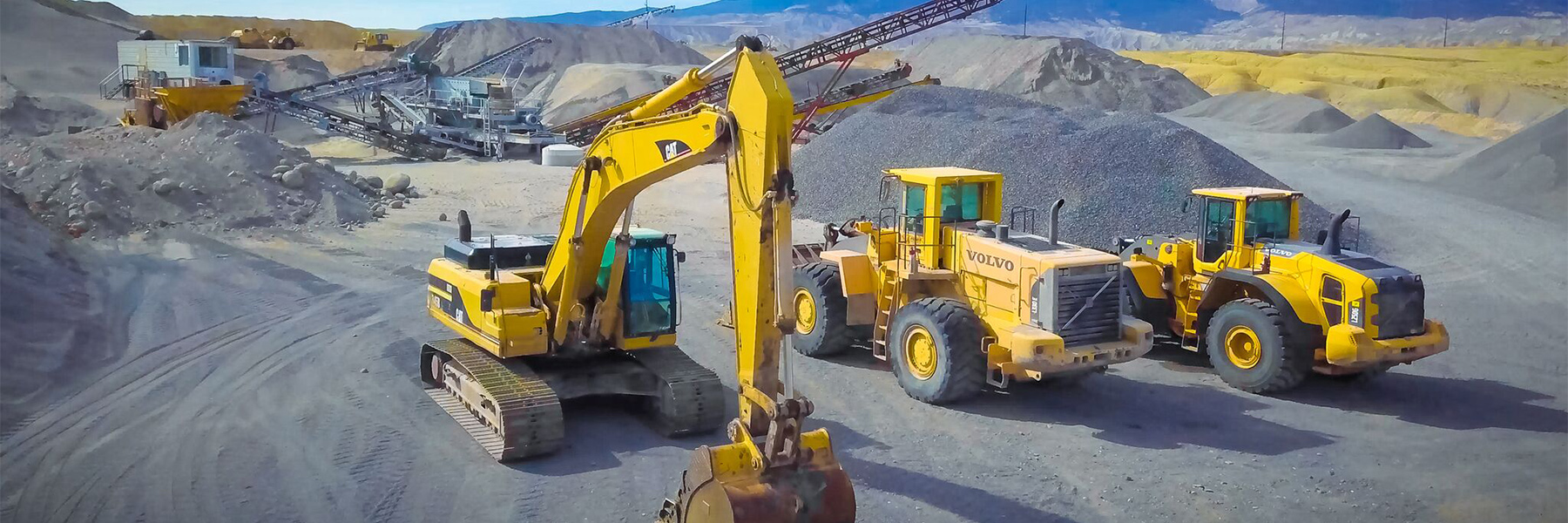 CAT excavator and two Volvo wheel loaders in gravel pit